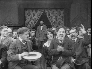 Chaplin causes havoc in a picture house and later in a film studio in A Film Johnnie.