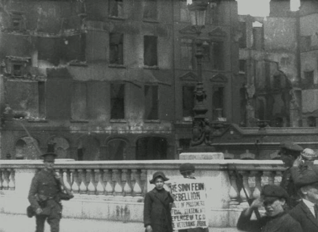 Framegrab from Easter Rising, Dublin 1916 (IWM 194) showing newsboys selling the Irish Times of 3 May 1916 against the ruins of Eden Quay.